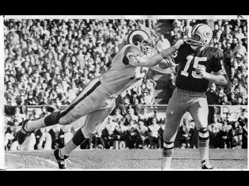 "Ram defensive end David ""Deacon"" Jones, left, forces Green Bay's Bart Starr to throw an incomplete"